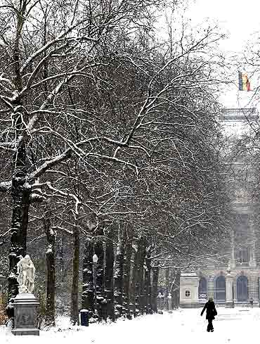 A woman walks towards the snow-covered Royal Park in front of The Royal Palace in Brussels