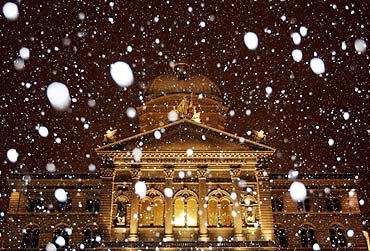 Snow falls in front of Switzerland's federal parliament building in Bern
