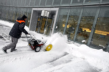 A man clears the snow away from the front of a business centre in Warsaw