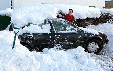 David Morran clears snow off his car as he trys to free it out of the driveway of his home in Braco, Scotland