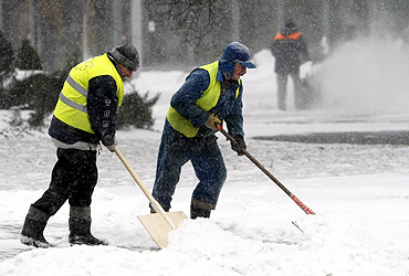 Men clear the snow away from a street in Warsaw
