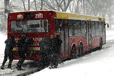Passengers push a bus during heavy snowfall in Lublin, eastern Poland
