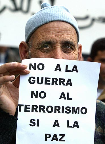 A man holds a poster reading 'No War, No Terrorism, Yes to Peace' in Madrid