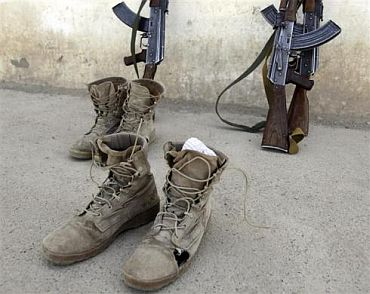 Afghan soldiers' boots with holes are left by a wall
