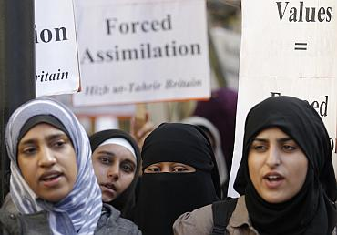 : Muslim woman take part in a demonstration by the Islamic political party Hizb ut-Tahrir against France's banning of full face veils from public spaces, outside the French Embassy in London