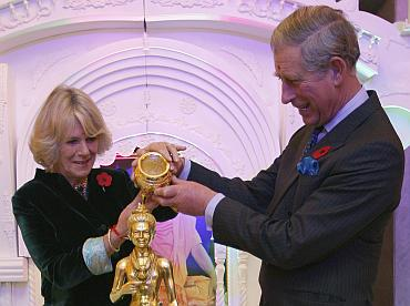 Britain's Prince Charles and Camilla, Duchess of Cornwall (L), pour holy water over a Murti figure during their visit to the Shri Swaminarayan temple in northwest London