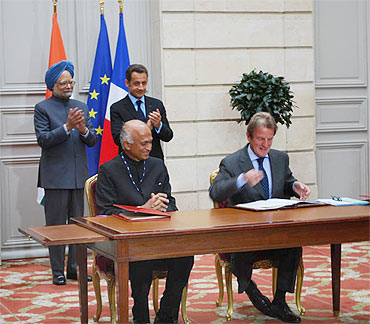 India's Ambassador Ranjan Mathai and French Foreign Minister Bernard Kouchner sign the agreement