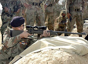 Pakistan Army chief General Ashfaq Parvez Kayani Kayani fires a sniper rifle during his visit to Tilla Field Firing Ranges