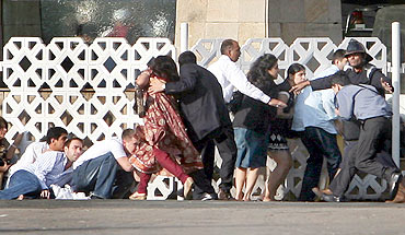 People duck as gunshots are fired from inside the Taj Mahal hotel in Mumbai during the 26/11 terror attacks