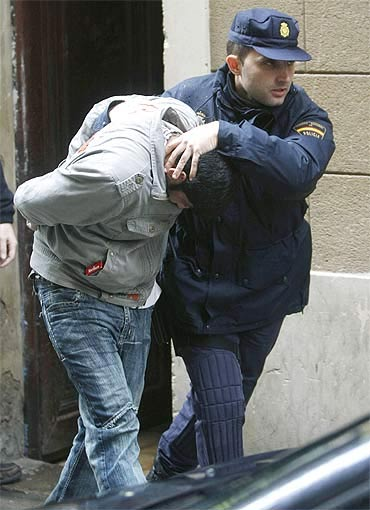 Police officers take an arrested man into a car after a police operation in Barcelona.