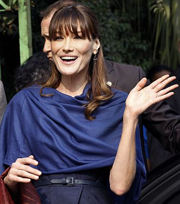French first lady Carla Bruni-Sarkozy waves local residents and journalists