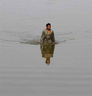 A man wades through floodwaters as he returns to his village in Sindh province