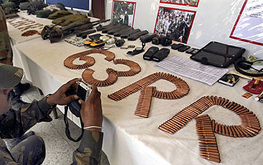 A soldier takes pictures of seized ammunition from Lashkar militants
