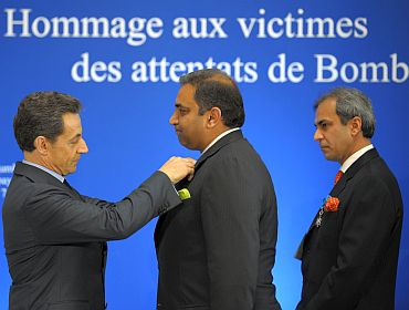 Sarkozy awards Director of the Taj Mahal Palace Karambir Kang (C) and Oberoi Hotel Vice President Devendra Bharma (R) during a ceremony in remembrance of the victims of the November 2008 attacks