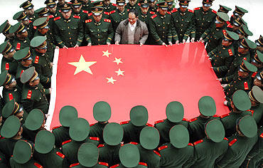 Paramilitary soldiers hold the Chinese national flag during a photo session at an army base in Taizhou, Zhejiang province