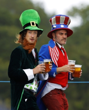 Britons dressed up in fancy costumes carry cups of beer
