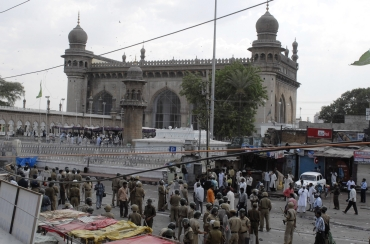 Policemen stand guard at the site of a bomb blast at Mecca Masjid