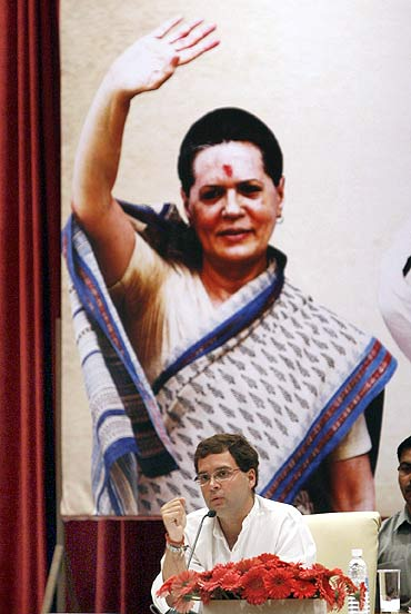 Rahul Gandhi addresses a press conference in front of a poster of his mother