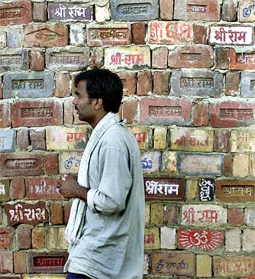 An activist walks past a temple wall, where devotees have written the name of Lord Ram, in Ayodhya
