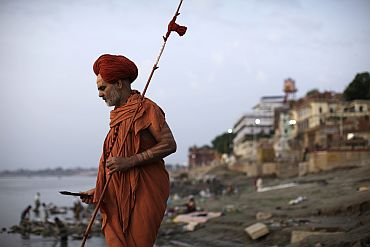 A holy man walks along the banks of the river Ganga in Varanasi
