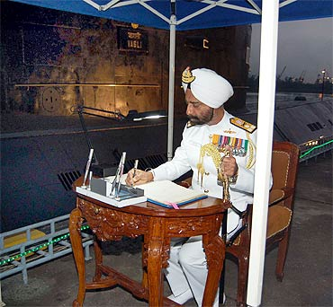 Vice Admiral Anup Singh signs the visitors' book of Vagli for the last time