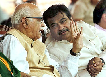 Senior Bharatiya Janata Party leader Lal Krishna Advani speaks with party president Nitin Gadkari during a rally in New Delhi