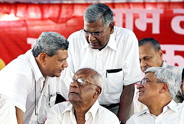 Senior Left leaders Sitaram Yechury (L), A B Bardhan, D Raja (C standing) and Prakash Karat (R) discuss during a rally in New Delhi