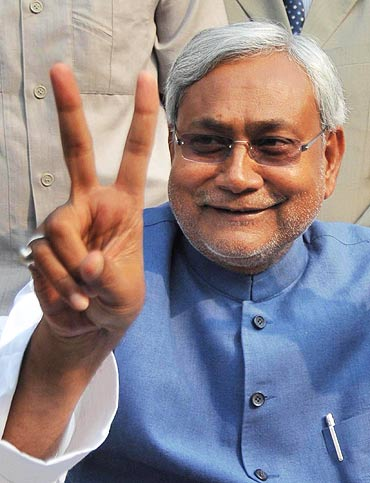 Bihar Chief Minister Nitish Kumar flashes a V-sign during a news conference in Patna after a thumping victory in state assembly polls