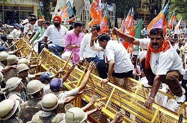 BJP activists face police try to stop them during a protest against the 2G scam