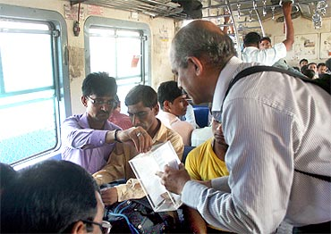 Professor Sandeep Desai collects donation on a Mumbai suburban train