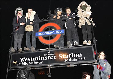 Demonstrators stand on an underground sign during a protest in Westminster