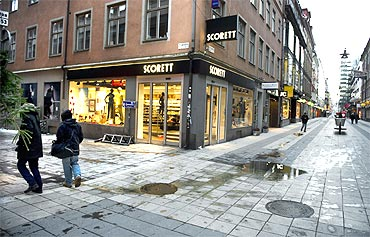 People pass a bomb blast site in central Stockholm