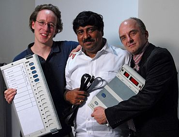 EVM report authors (left to right) J Alex Halderman, Hari K Prasad, and Rop Gonggrijp holding the EVM that they hacked into