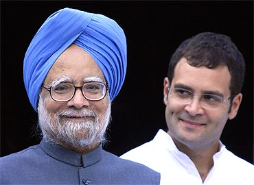 Prime Minister Manmohan Singh smiles as Rahul Gandhi watches during a meeting in New Delhi