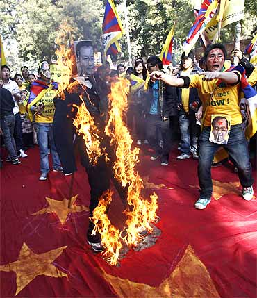 ibetan exiles burn an effigy and shout slogans during a protest march