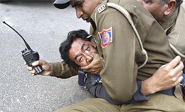 Police detain a Tibetan exile during a protest outside a Delhi hotel