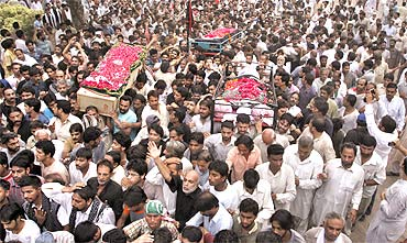 Men carry coffins of victims who were killed in a bomb blast in Lahore