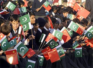 Pakistani school children hold Pakistani and Chinese national flags
