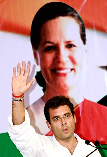 Rahul Gandhi sits in front of a poster of his mother and UPA chief Sonia Gandhi