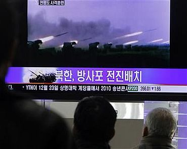 People watch a news report featuring old video footage of a North Korean firing drill, at a railroad station in central Seoul in this December 20 photo