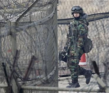 A South Korean Army soldier patrols along the military barbed wire fence near the demilitarised zone separating the two Koreas in Paju, north of Seoul