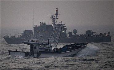 A fishing boat sails past a South Korean navy ship patrolling off Yeonpyeong Island