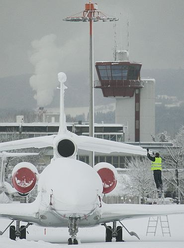 A airfield worker stands on a ladder as he removes snow from an aircraft parked on the tarmac of Zurich airport in Kloten after the region was hit by strong snow fall