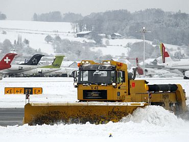 Workers use a snowplough to remove snow from the tarmac of Zurich airport