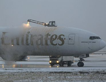 An Emirates aircraft is de-iced after heavy snowfall at Dusseldorf airport