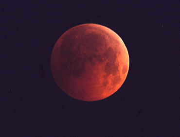 The Moon, appearing a dim red colour, is covered by the Earth's shadow