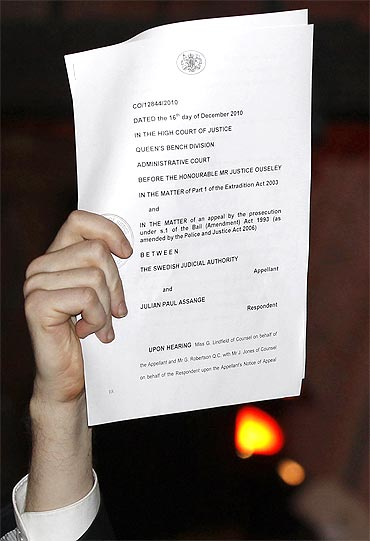 Assange holds up a court document as he emerges to speak to the media on the steps of the High Court in London