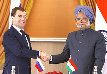 Russia's President Dmitry Medvedev (L) shakes hands with PM Manmohan Singh after signing of agreements ceremony in New Delhi on Tuesday