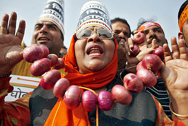 A BJP supporter wears a garland made of onions