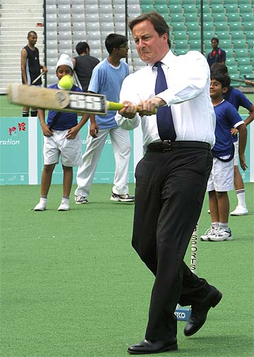 British Prime Minister David Cameron plays cricket inside a stadium in New Delhi